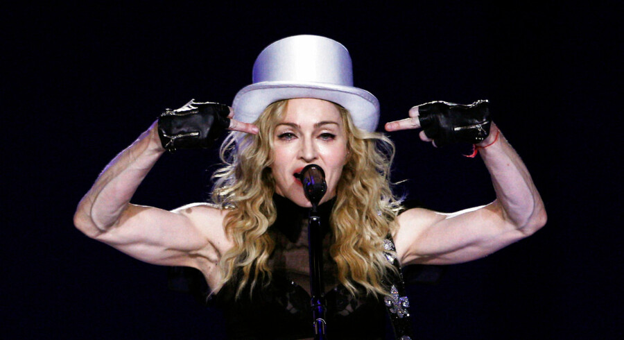 U.S. singer Madonna gestures as she performs during her Sticky and Sweet tour at the O2 Arena in London in this file photo taken July 4, 2009. The entertainer celebrates her 55th birthday on August 16. REUTERS/Luke MacGregor/Files (BRITAIN - Tags: ENTERTAINMENT)