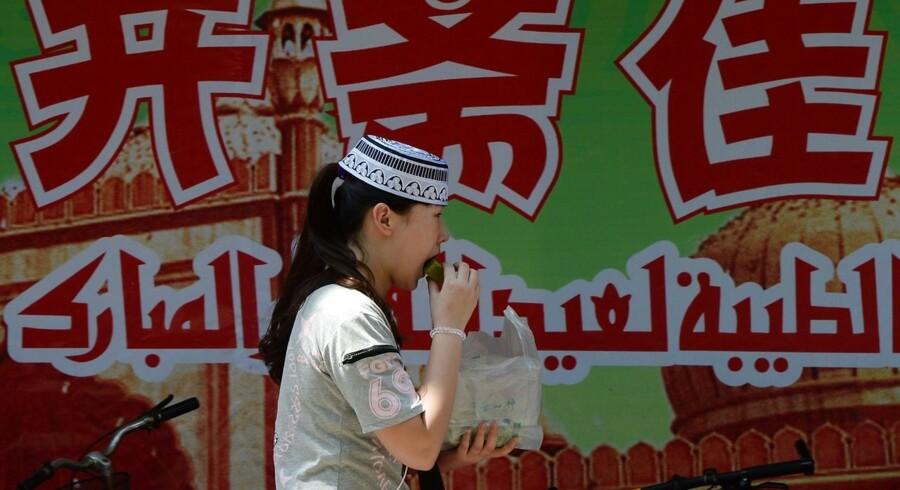 Kinesisk hui-muslim fejrer at fasten er slut med en kage ved den historiske Niujie Moske i Beijing.