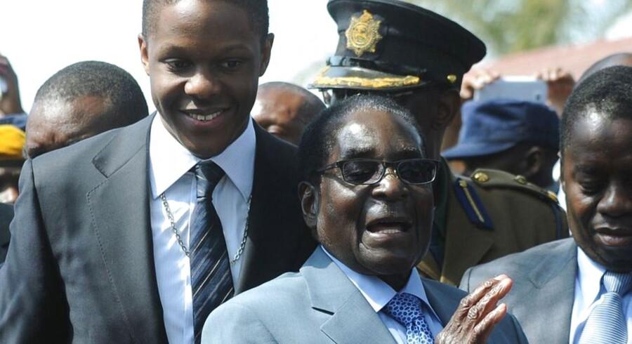 Zimbabwes præsident Robert Mugabe (th) og hans søn Bellamine (tv) forlader et valgsted i Harare i sidste uge.