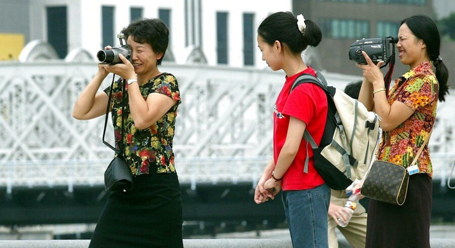 Two Chinese tourists are busy capturing the scenery while a young Chinese girl (C) looks on.