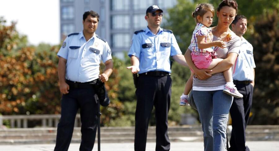 En kvinde bærer sit barn væk fra politiaspærringen ved indgangen til Gezi-parken, der er omdrejningspunktet for striden mellem demonstranter og myndigheder.
