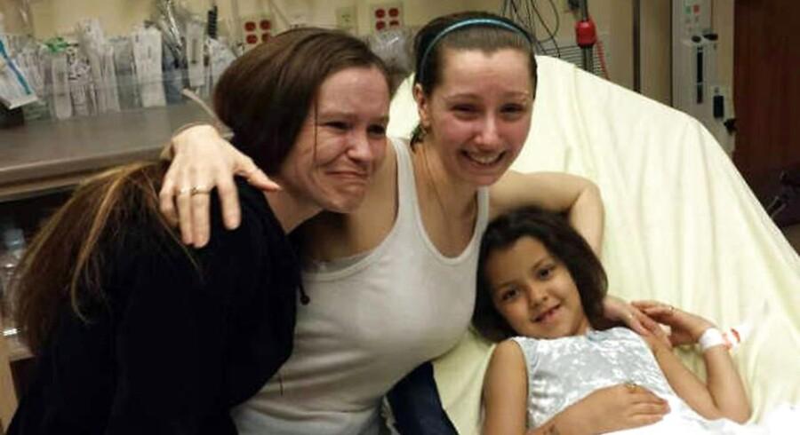 Pigen yderst til højre er kidnapningsoffer Amanda Berrys (i midten) datter. Og en DNA-test viser nu, at hendes far er Ariel Castro, der er anholdt og sigtet for at have bortført Berry og to andre kvinder fro cirka 10 år siden. Billedet her er taget på hospitalet kort efter, at Berry tog flugten fra sin bortførers hus i Cleveland, Ohio. Til venstre er det Berrys søster, der blev genforenet med sin søster på hospitalet.