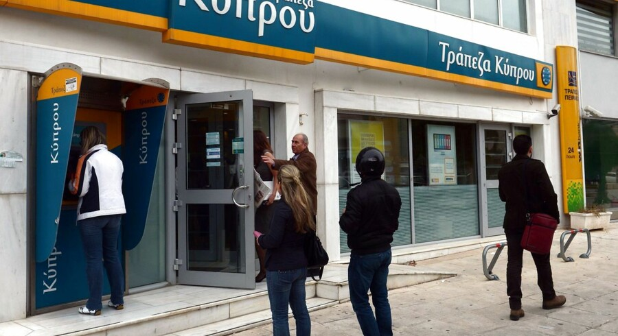People enter a Bank of Cyprus branch in Athens on March 27, 2013, as Greek subsidiaries of three Cypriot banks reopened today after Greece's third lender, Piraeus bank, signed an agreement to acquire all their deposits, loans and branches. But banks in Cyprus itself remained closed as authorities worked out a plan to get them back up and running amid the country's financial crisis. AFP PHOTO / ARIS MESSINIS