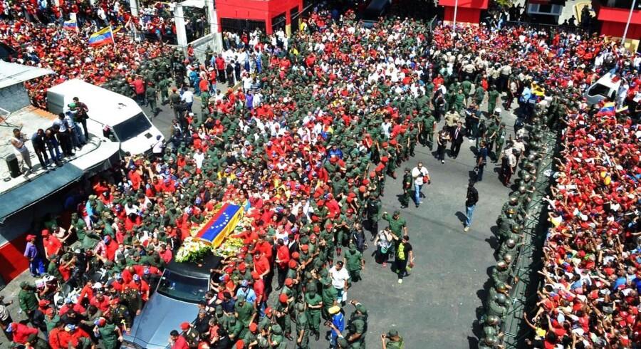 Titusinder af sørgende Hugo Chavez-tilhængere fører kisten med Venezuelas afdøde præsident gennem Caracas' gader.