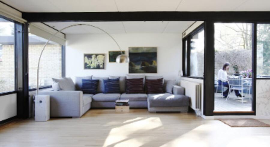 I stuen er der – som mange andre steder i huset – markante sorte bjælkepartier, og her indrammer de effektfuldt sofahjørnet. De store vinduer inviterer masser af dagslys indenfor. Den grå sofa er fra BoConcept, og Achille & Pier Giacomo Castiglioni´s Arco Floor Lamp er købt på auktion. Puderne er fra Bolia. En vinkasse fungerer som mini-sofabord.