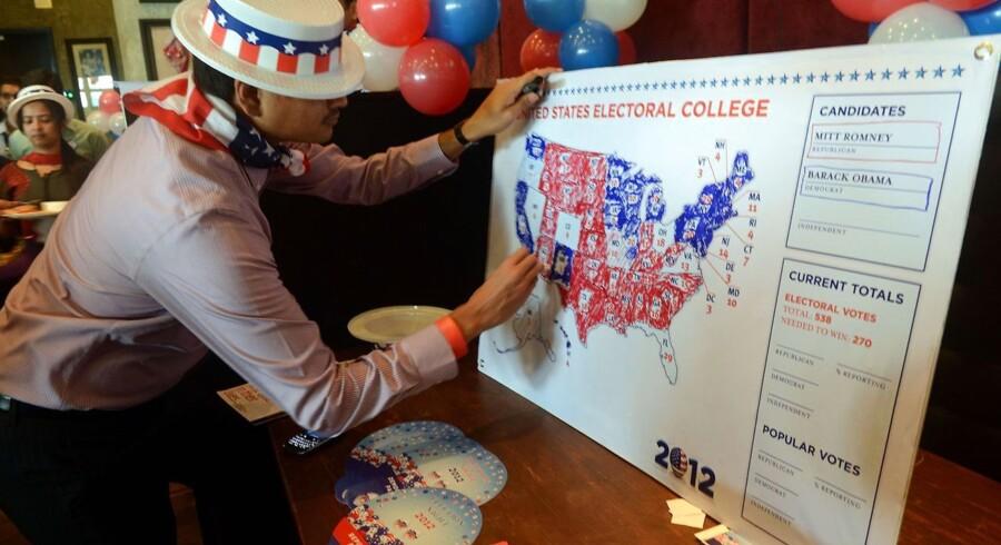 En medarbejder på det amerikanske konsulat i Mumbai gør valgresuoltaterne synlige på et kort. New York Times-bloggeren Nate Silver forudså valget i samtlige 50 stater.