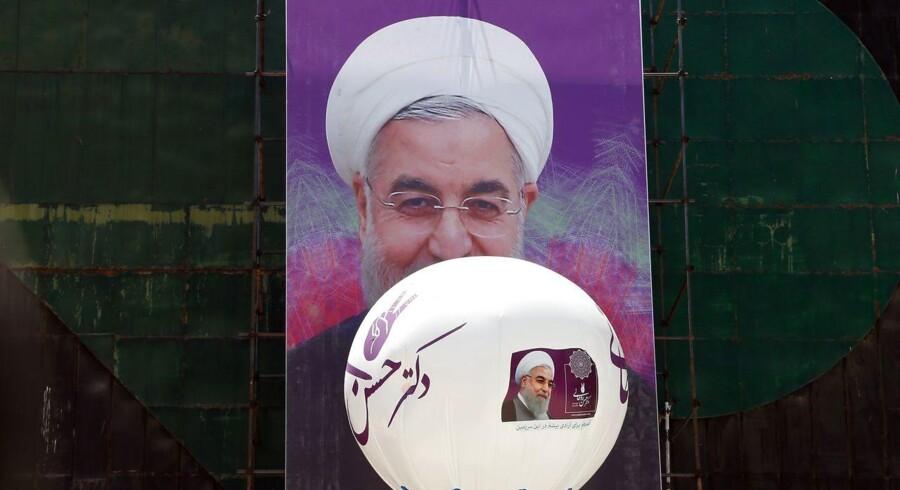 epa05975888 Den hvide turban vandt over den sorte. Hassan Rouhani blev fredag genvalgt som Irans præsident. HAn vandt over den konservative kandidat Ebrahim Raisi. Her ses en ballon flyve forbi en stor plakat af Rouhani i Teheran. EPA/ABEDIN TAHERKENAREH