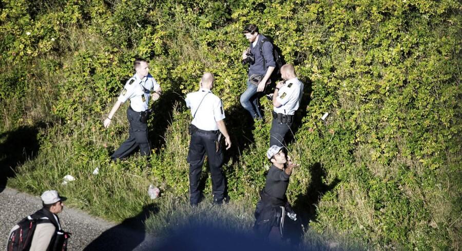ARKIVFOTO 9.september 2015 af Politikens fotograf Martin Lehmann (bagerst), der angiveligt bliver anholdt efter politiet har bedt pressen fjerne sig fra den gruppe flygtninge, der går på motorvejen nord for Padborg