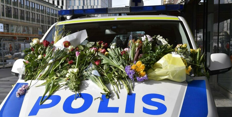 epa05898706 People leave flowers on a police van outside Ahlens department store following the 07 April terror attack in central Stockholm, Sweden 09 April 2017. A hijacked beer truck ploughed into pedestrians on Drottninggatan and crashed into Ahlens department store, killing four people, injuring 15 others late 07 April 2017. EPA/JONAS EKSTROMER SWEDEN OUT