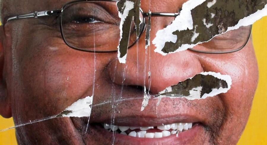 Sydafrikas præsident, Jacob Zuma - her afbilledet på en iturevet valgpalkat - er under voldsom pres for at træde tilbage. EPA/KIM LUDBROOK