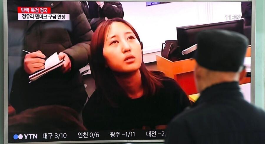 Folk kigger på en TV-skærm, hvor nyheden om Chung Yoo-Ras anholdelse bliver rapporteret.