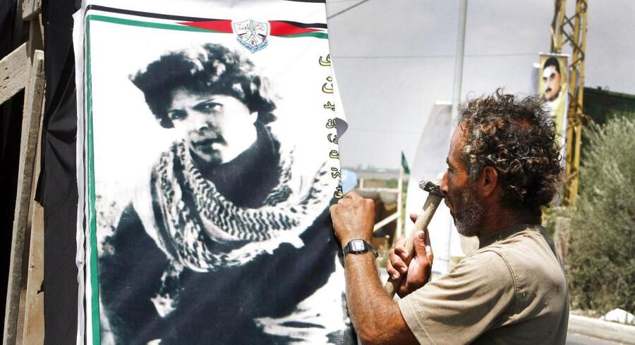 BMINTERN - En libanesisk mand hænger et billede af Dalal al-Mughrabi op på en pæl. I 2008 skulle Israel udlevere resterne af den afdøde Dalal al-Mughrabi i forbindelse med en fangeudveksling mellem Israel og Hizbollah. Men Israel hævdede, at man ikke kunne finde al-Mughrabis knogler på statens gravsted for terrorister. Dalal al-Mughrabi anførte i 1978 et terrorangreb mod civile israelere nord for Tel Aviv. 38, inklusive 13 børn, blev dræbt AFP PHOTO/RAMZI HAIDAR. RAMZI HAIDAR / AFP
