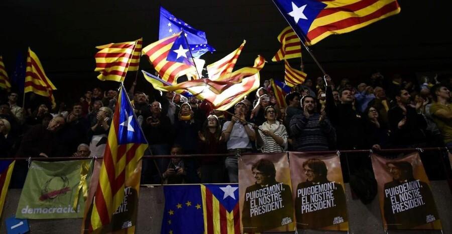Folk med catalanske pro-independence 'Estelada' flag under et kampagnemøde med 'Junts per Catalonien' - JUNTSXCAT (Alt for Catalonien) grupperingen for det kommende catalanske regionale valg i Barcelona den 15. december 2017 (Foto: JAVIER SORIANO/Scanpix 2017)