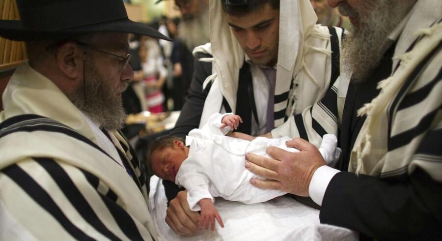 En ortodoks jødisk far holder sin søn, før den rituelle omskæring på barnets ottende levedag. Arkivfoto.