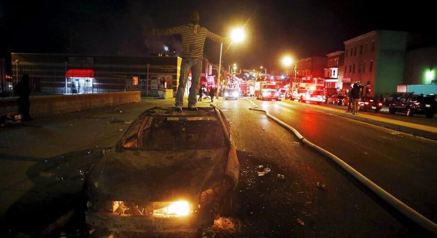 Bag den udbrændte bil kæmper brandmænd med at slukke ilden i adskillige bygninger.