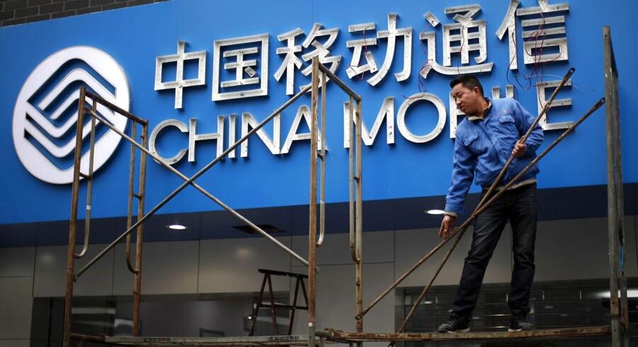 Kinas største mobilselskab, China Mobile, fortsætter med at høste store mængder af kunder. Her er en arbejder i gang med skiltet uden for China Mobiles kontor i Shanghai. Arkivfoto: Carlos Barria, Reuters/Scanpix