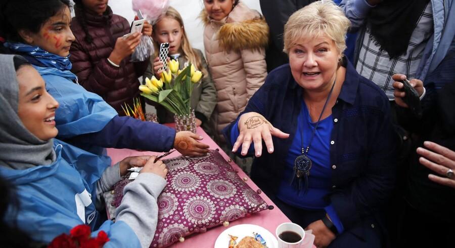 OSLO 20170909. Statsminister Erna Solberg (H) får hennamaling på hånden av Mifra Iqbal (tv) under på besøk på Mortensruddagene på Mortensrud i Oslo lørdag. Foto: Cornelius Poppe / NTB scanpix / TT / kod 20520. (Foto: 20520 Poppe, Cornelius/Scanpix 2017)