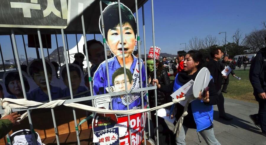 Demonstranter har smidt en papfigur af den sydkoreanske præsident, Park Geun-hye, bag tremmer efter afgørelsen om, at hun skal retsforfølges.