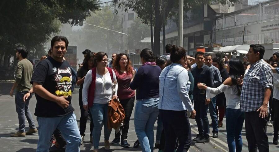 Tusinder af mennesker er flygtet ud af bygningerne og befinder sig i storbyens gader. / AFP PHOTO / Yuri CORTEZ