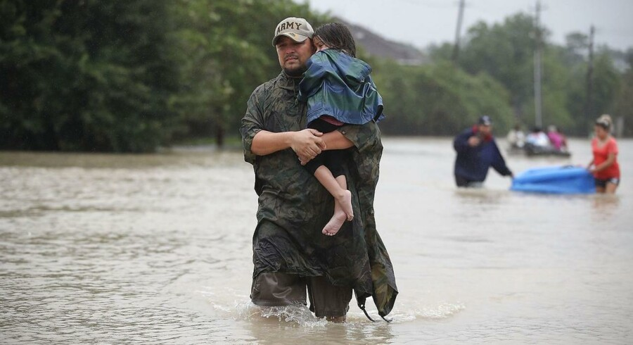 Folk går ned ad en oversvømmet gade i forsøget på at evakuere så meget som muligt fra deres hjem.