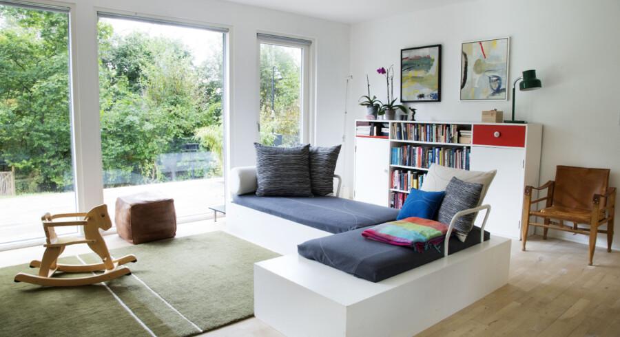 Den grønne udsigt fra husets stue gør Nanna Schou så glad. Sofaen har parret selv bygget, og den passer til rummet, blandt andet fordi den ikke skærmer for lyset, der strømmer ind ad de store vinduespartier.