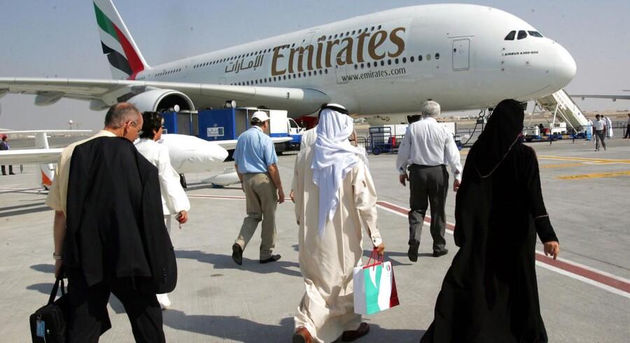 Vestligt og arabisk påklædte flyrejsende på vej om bord på et Emirates-fly i lufthavnen i Dubai.