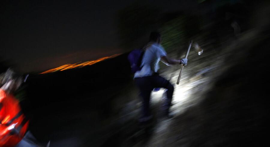 Frivillige på vej op ad et bjerg for at rydde et brændt område nær Malaga.