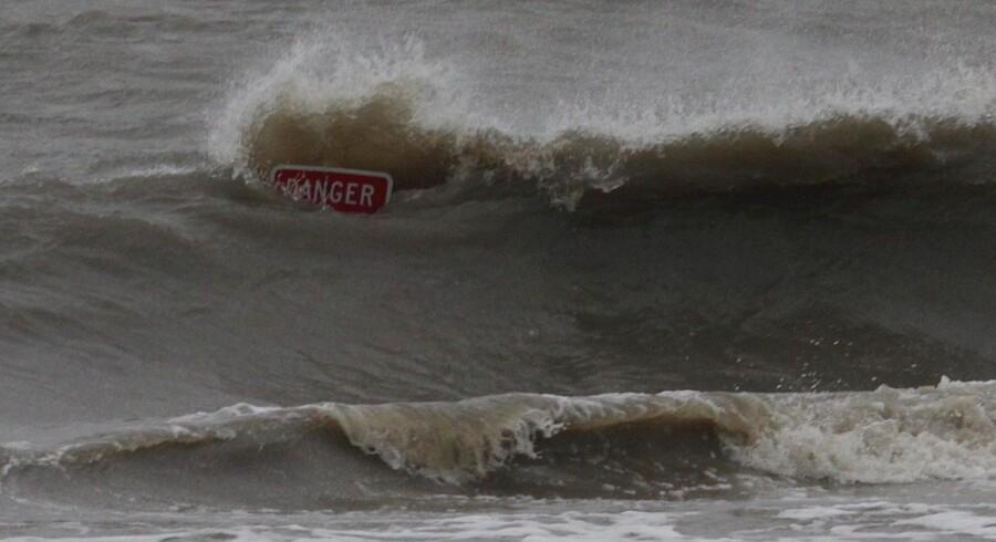 Stormen Isaac har ramt USAs østkyst med oversvømmelser og strømafbrydelser til følge. Bølgerne bruser omkring et advarsels skilt i Mississippi.