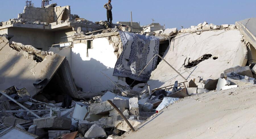 En mand står på et hus som blev smadret ved luftangrebet mod byen Azaz, nord for Aleppo. Mange civile døde ved angrebet.