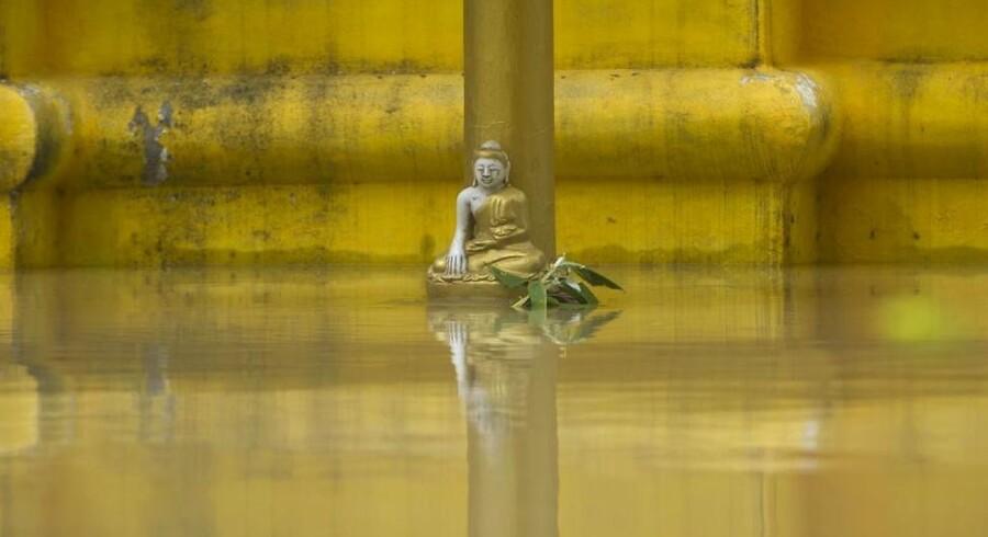 En buddha-statue i landsbyen Kyouk Ye i Myanmar er stadig over vandet fra floden Irrawaddy, der stiger efter kraftig monsunregn.
