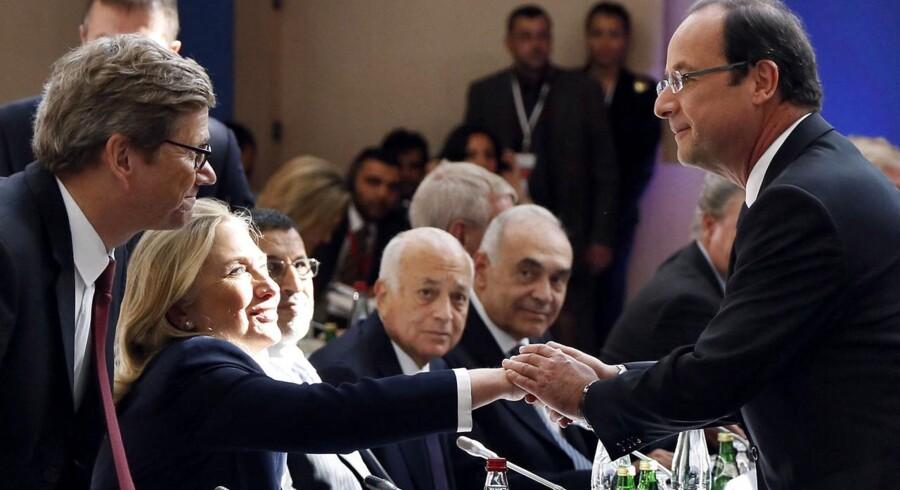Mødet mellem »Syriens venner« i Paris fredag 6. juli 2012. Her USAs udenrigsminister Hillary Clinton - flankeret Tysklands udenrigsminister Guido Westerwelle (tv) - giver hånd til Frankrigs præsident Francois Hollande.