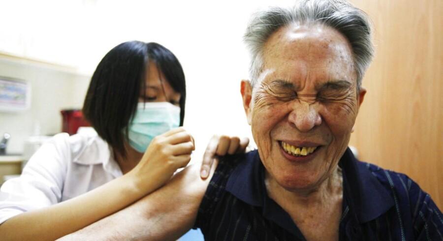 En mand i Taiwan skærer ansigt, som han vaccineres mod H1N1 og lungebetændelse.