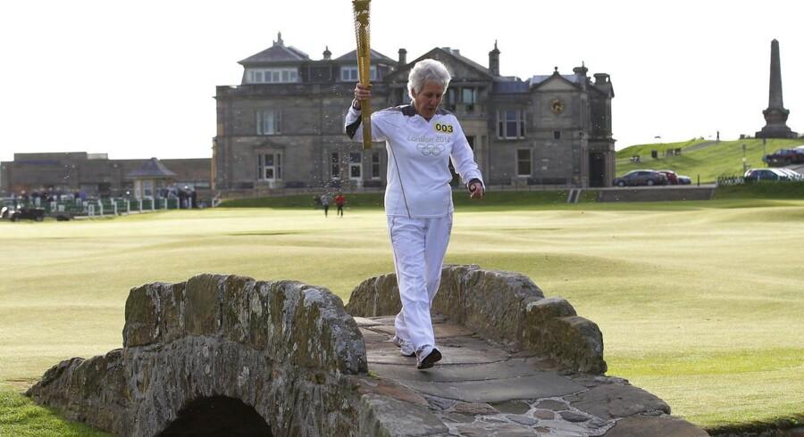Fakkelbærer Louise Martin løber med faklen for London 2012 over Swilken Bridge ved 18. hul ved golfbanen St. Andrews i Skotland.