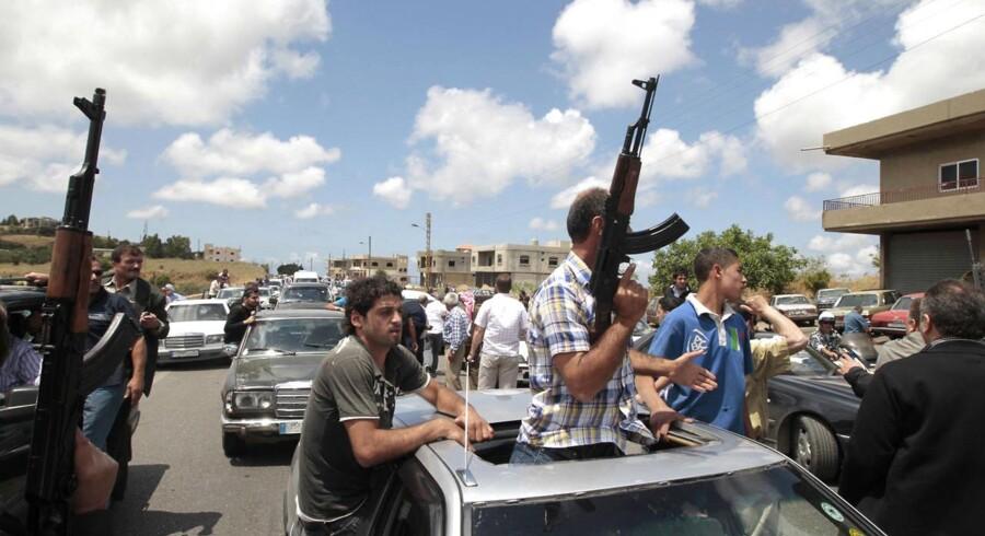 Bevæbnende sunnimuslimer eskorterer ambulancen med den dræbte sheik.