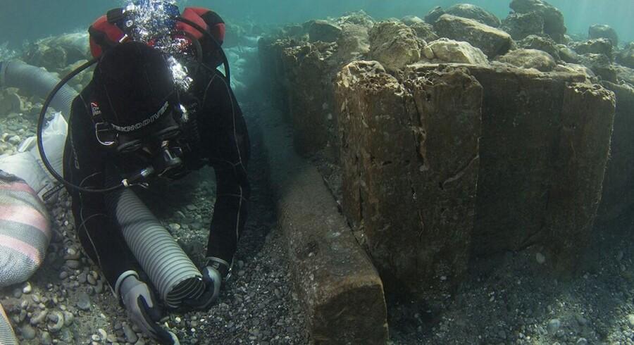 En arkæolog undersøger området, hvor man har identificeret rester fra den oldgræske havneby Lechaion.