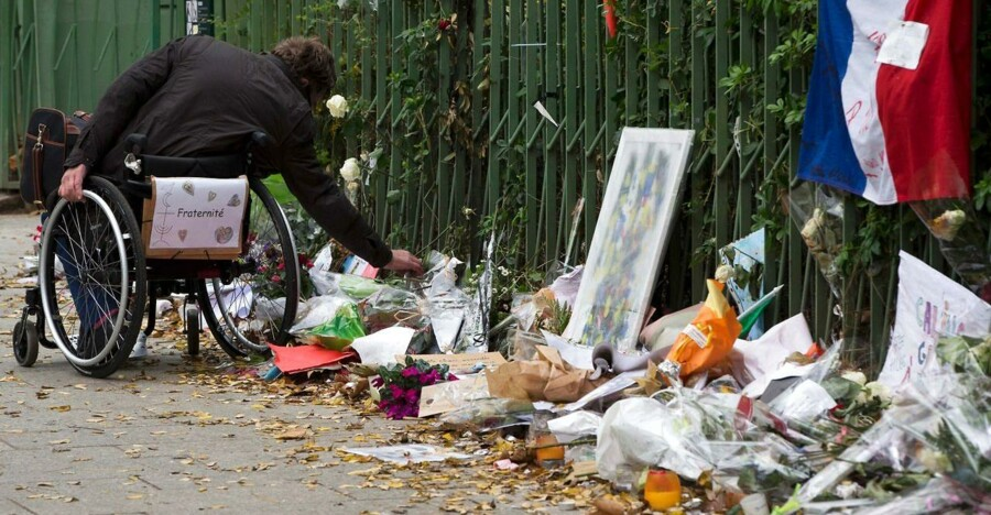 A man in a wheelchair pays tribute to the victims of the November 13 terror attacks at a makeshift memorial near the Bataclan concert hall in Paris on December 10, 2015. Drawings, messages, photographs, flowers or teddy bears will be stocked in the Paris city hall's archives to testimony the events of November 13, 2015. / AFP / JOEL SAGET