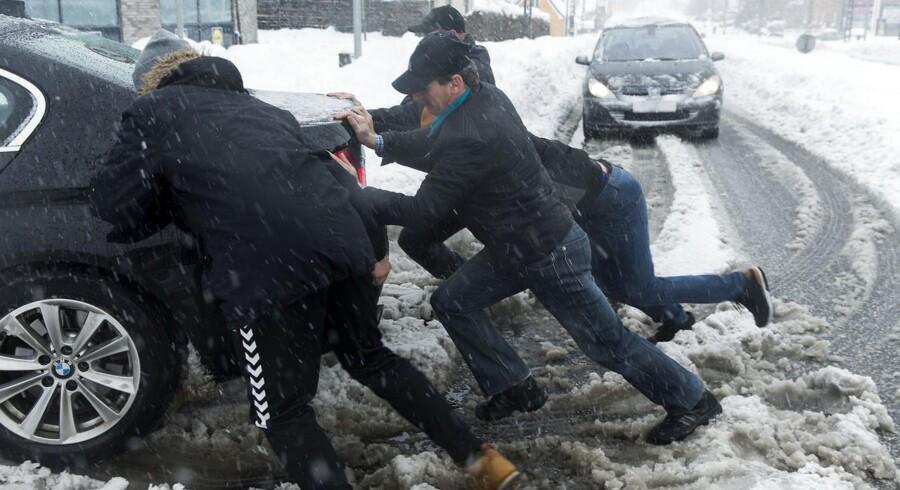 Vinterens første sne og slud giver store problemer for trafikken. Bil skubbes fri på Københavnsvej i Roskilde.