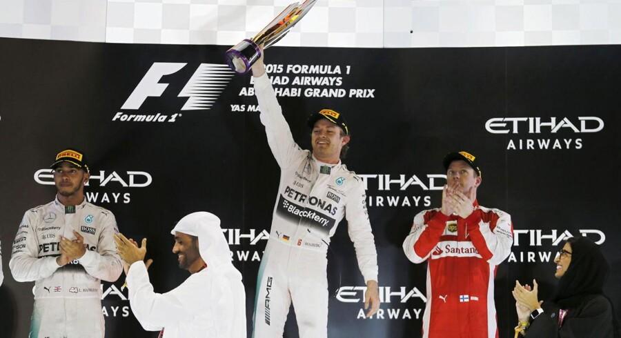 Nico Rosberg (im) fejrer at have vundet grand-prix'et i Abu Dhabi. Til venstre ses nummer to, Lewis Hamilton, der blev en klar samlet vinder, mens Kimi Räikkönen blev nummer tre i Abu Dhabi - og nummer fire samlet.