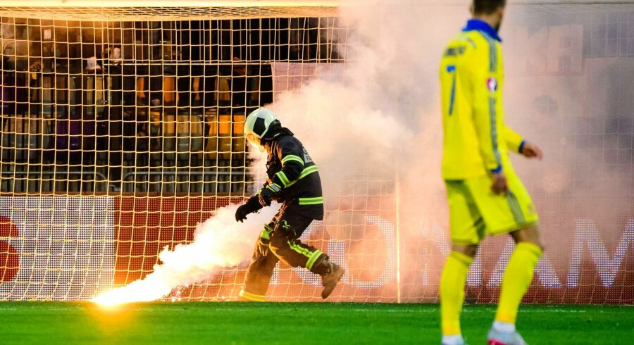 A firefighter rushes to remove a torch as Slovenia's fans celebrate during the Euro 2016 play-off football match between Slovenia and Ukraine the Ljudski stadium in Maribor, on November 17, 2015. AFP PHOTO / JURE MAKOVEC