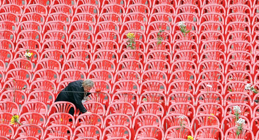En ældre kvinde lægger blomster ved en af stolene. Konflikten i Bosnien var en af de blodigste siden Anden Verdenskrig.