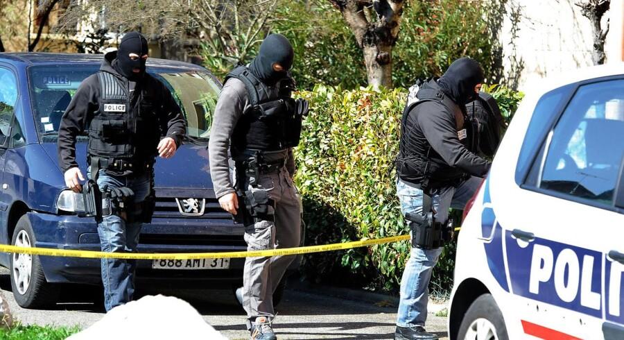 Hætteklædte franske betjente ransager den dræbtes hjem.