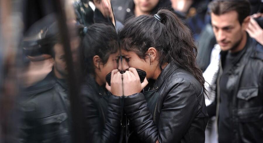 """En kvinde græder, mens hun står op ad en af bilerne, der fragtede kisterne med de døde efter en begravelsesceremoni på den jødiske skole """"Ozar Hatorah"""" den 20. marts 2012 i Toulouse i det sydvestlige."""