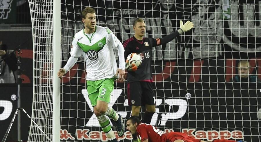 Nicklas Bendtner (tv) har scoret for VfL Wolfsburg mod Bayer Leverkusen, hvis målmand, Bernd Leno, protesterer.