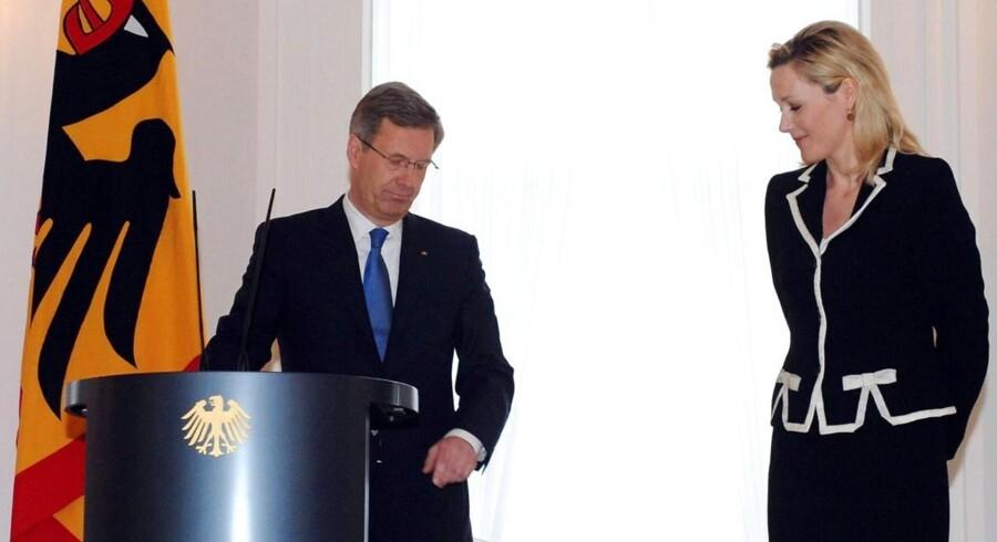 Christian Wulff (tv) begærer sin afsked ved en pressekonference flankeret af sin hustru Bettina.