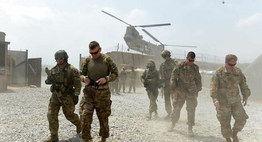 """TO GO WITH AFGHANISTAN-US-ARMY-CONFLICT-FOCUS BY GUILLAUME DECAMME In this photograph taken on August 13, 2015, US army soldiers walk as a NATO helicopter flies overhead at coalition force Forward Operating Base (FOB) Connelly in the Khogyani district in the eastern province of Nangarhar. From his watchtower in insurgency-wracked eastern Afghanistan, US army Specialist Josh Whitten doesn't have much to say about his Afghan colleagues. """"They don't come up here anymore, because they used to mess around with our stuff. """"Welcome to Forward Operating Base Connelly, where US troops are providing training and tactical advice to the 201st Afghan army corps as they take on the Taliban on the battlefield. AFP PHOTO / Wakil Kohsar"""
