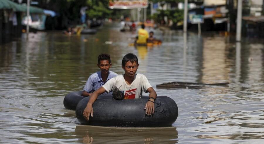Kraftig monsunregn i Myanmar har i løbet af den seneste måned kostet mindst 27 mennesker livet og fordrevet mere end 150.000, oplyser FNs kontor for koordinering af humanitær indsats.To mænd vader gennem byen »Kalay« med gummiringe rundt om sig.Klik videre for at se flere billeder af oversvømmelsen.