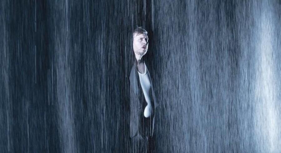 Nicolas Bro som den hjemvendte kunstnersøn i første afdeling af forestillingen, der foregår i silende regn foran et mørkt tæppe.