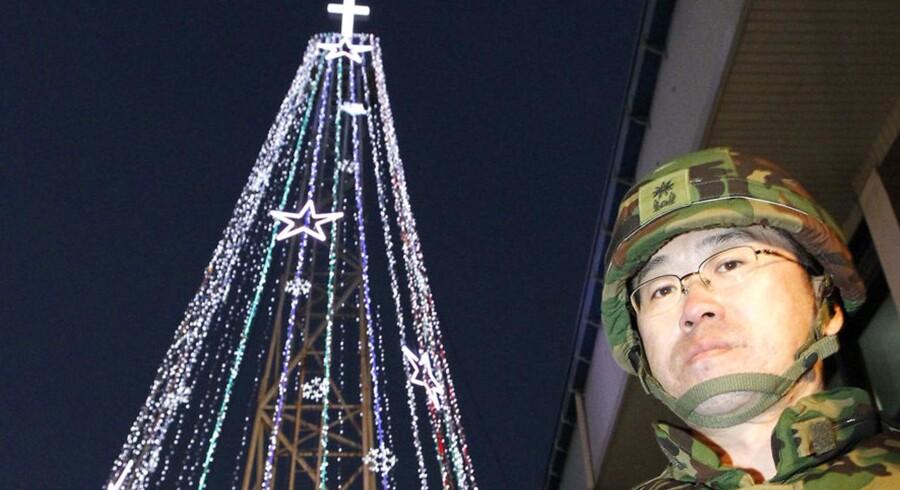 En sydkoreansk soldat står på vagt, mens kristne gør det store metal-juletræ klar tilindvielsesceremonieni 2010. I år opruster Sydkorea deres julearsenal, når de opstiller to oplyste juletræs-formede tårne.