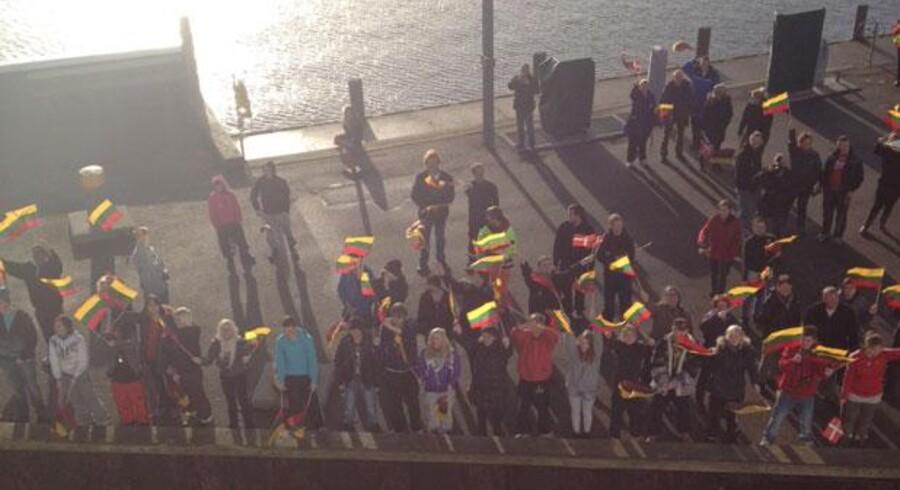 Passagererne bliver modtaget med flag på havnen i Ærøskøbing. De er om bord på færgen, der har været strandet på en sandbanke til havs siden søndag eftermiddag. Privatfoto.