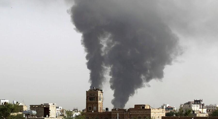 Tyk røg stiger mod himlen, efter et luftangreb har ramt Yemen. Knap 100 personer har mandag mistet livet i luftangreb i landet.
